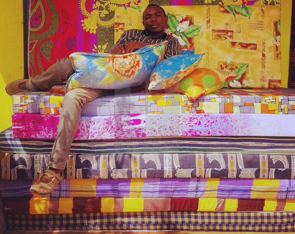 A man sitting on a pile of memory foam mattresses
