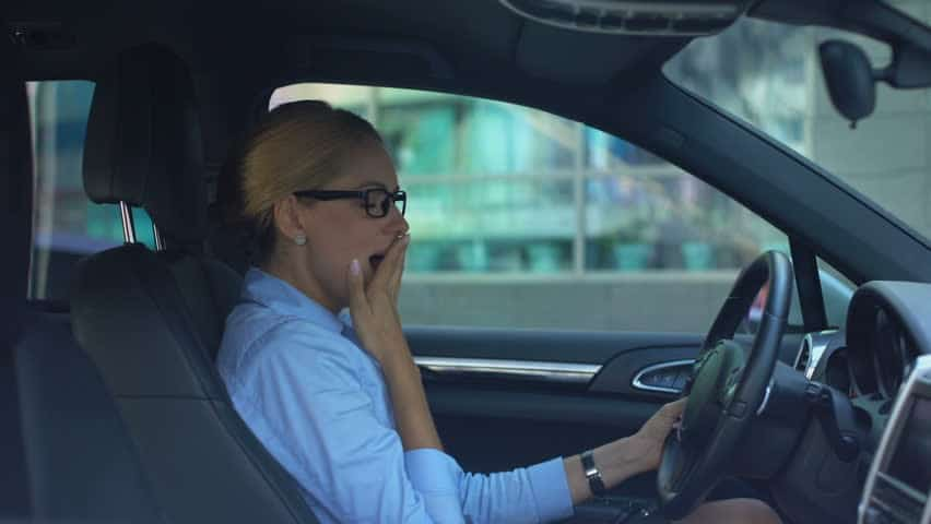 A woman tired while driving