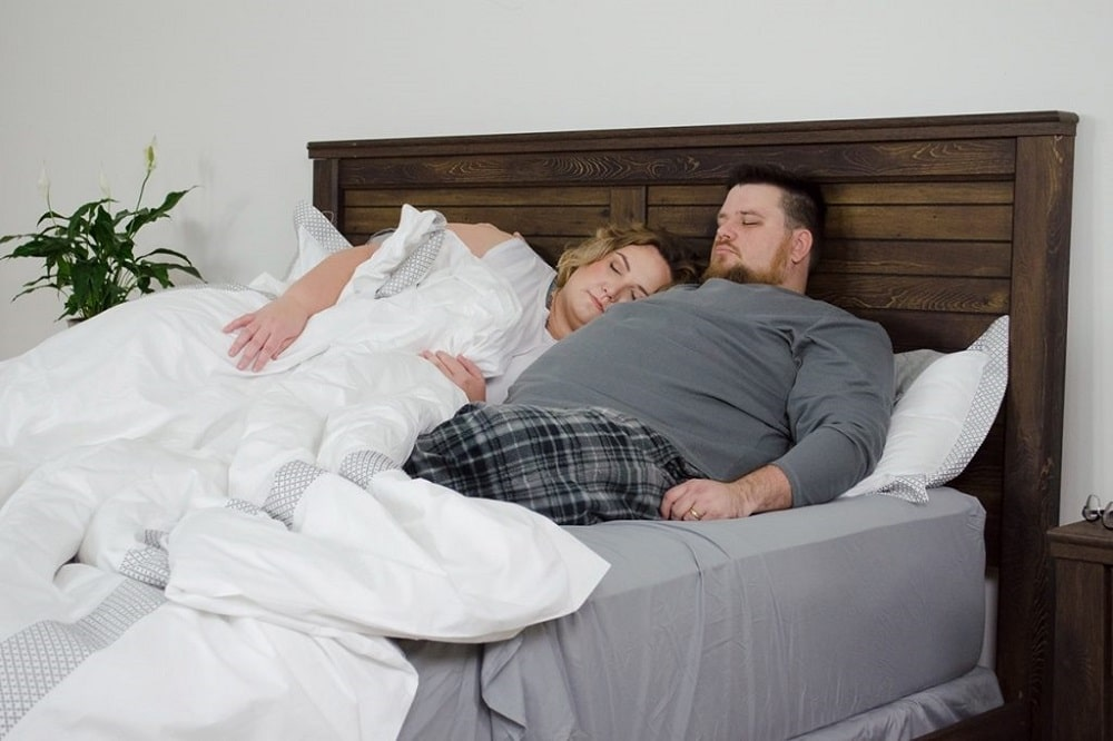 Fat overweight couple sleeping on a mattress